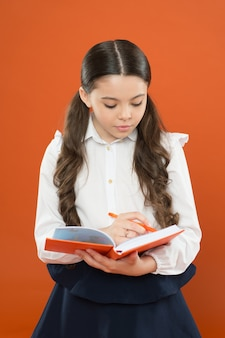 Schoolgirl writing notes on orange background reading lesson get information form book
