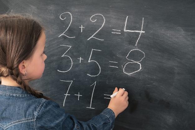 Schoolgirl writning math sums in chalk on blackboard