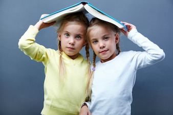 Schoolgirls playing with an open book