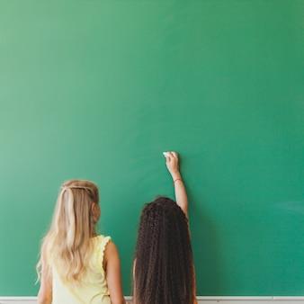 Schoolgirls standing at chalkboard