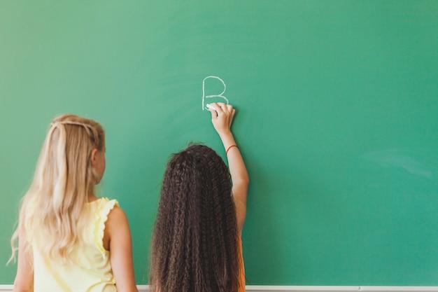 Schoolgirls standing in front of chalkboard