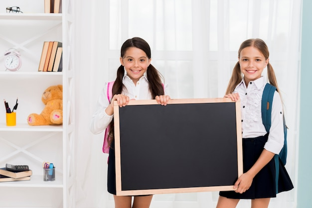 Schoolgirls in uniform with chalkboard