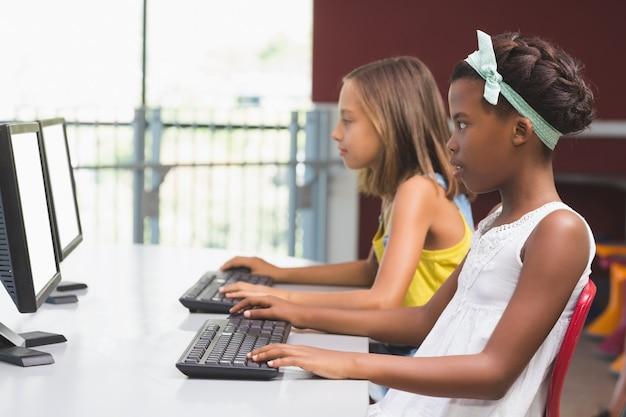 教室でコンピューターを使用する女子学生