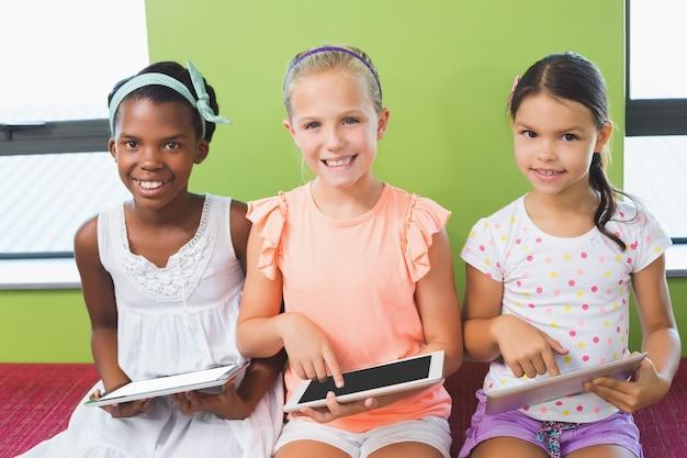 Школьницы с помощью цифрового планшета в библиотеке
