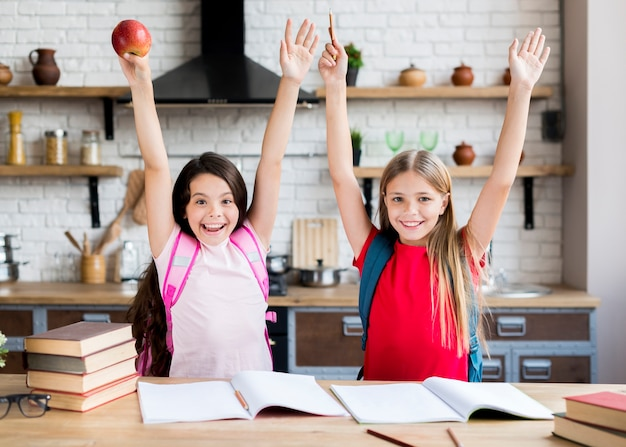 Schoolgirls with hands up standing in kitchen