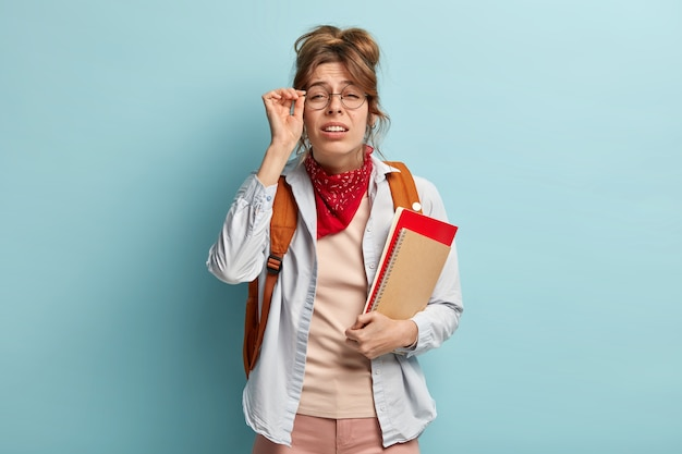 Schoolgril con cattiva vista cerca di vedere qualcosa in lontananza, tiene la mano sulla montatura degli occhiali