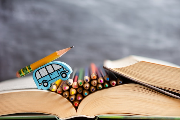 教育。子供の車が鉛筆で本に乗る