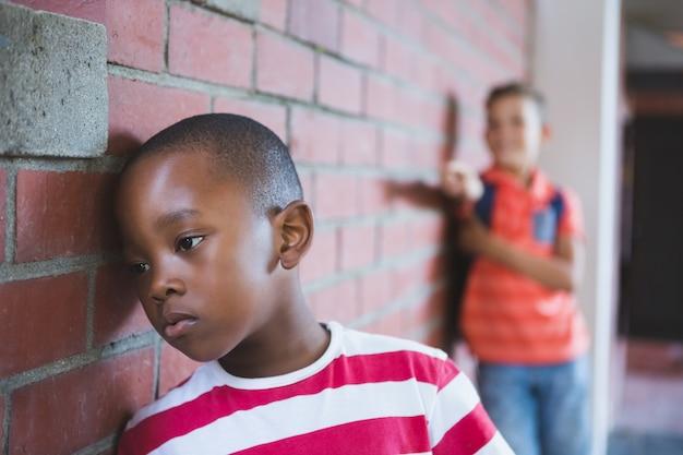 Schoolkid bullying a sad boy in corridor