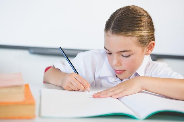Schoolkid doing homework in classroom