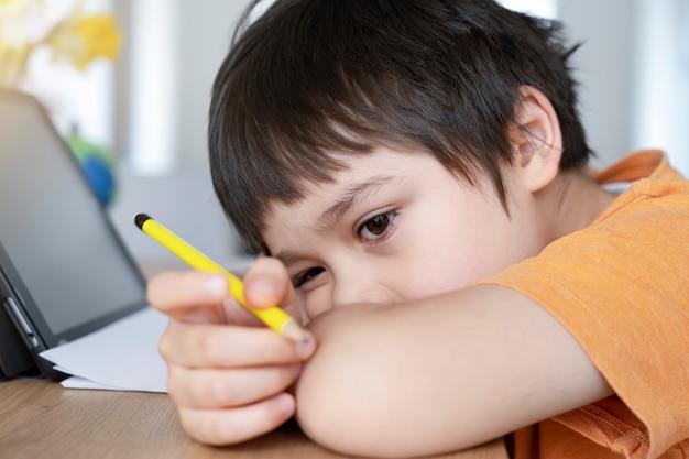 Школьник в самоизоляции, используя планшет для домашней работы, скучающее дитя, печальное лицо, опустив голову, смотрит глубоко в мысли,