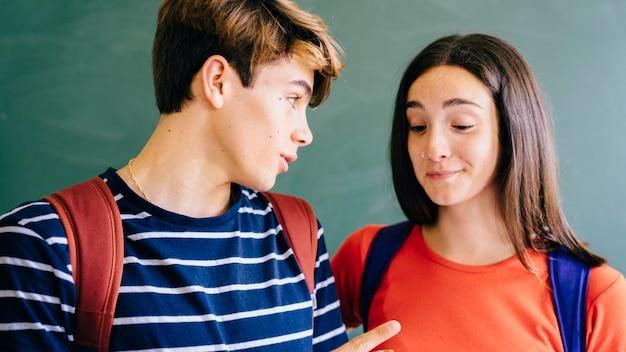 그의 친구에게 뭔가를 말하는 schoolkid