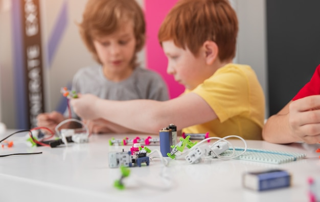 Школьники, изучающие роботизированные технологии в классе