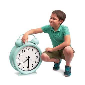 Schools start too early. little boy with large alarm clock.