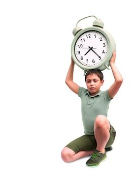 学校の開始が早すぎます。大きな目覚まし時計を持つ小さな男の子。