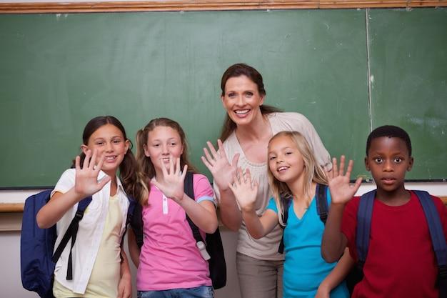 学校の先生とカメラに手を振る生徒