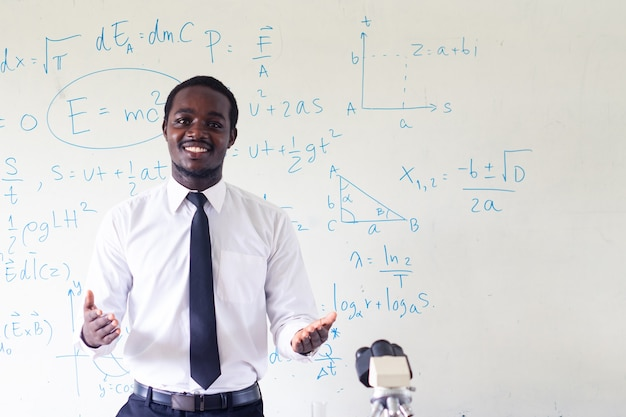 Science african teacher standing in front of blackboard teaching student in classroom