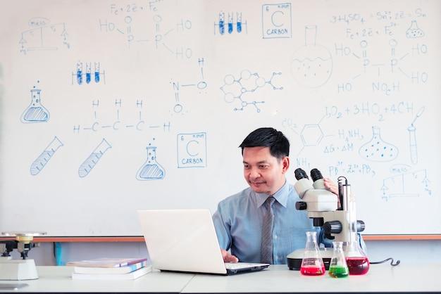 Учитель химии преподает онлайн с микроскопом и ноутбуком в классе