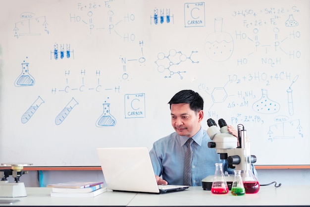Science chemistry teacher teaching online with microscope and laptop in the classroom
