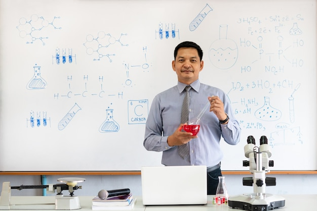 Учитель химии преподает с микроскопом и ноутбуком в классе