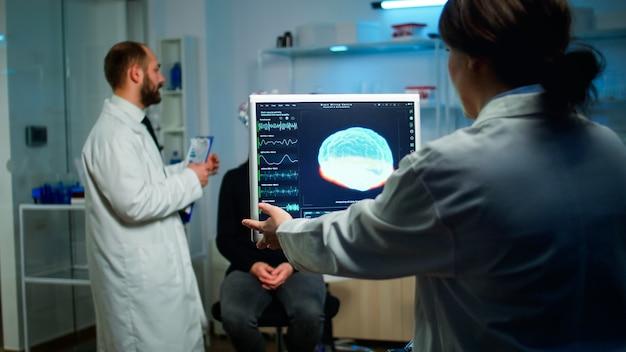 Врач-ученый смотрит на компьютер с фильмом о медицинском сканировании мозга, показывающим на мониторе в неврологической клинике