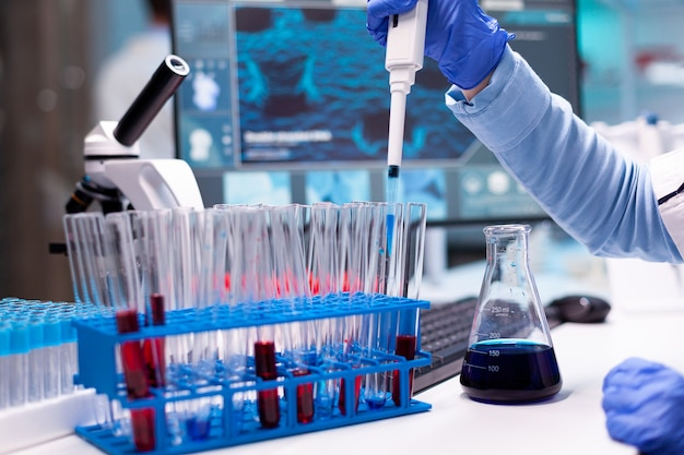 Science doctor in pharmaceutical lab uses micropipette to take sample