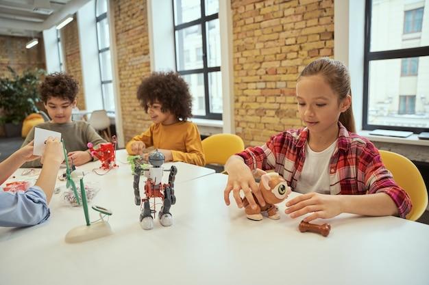 과학은 어디에서나 긍정적인 다양한 아이들이 앉아 있는 엔지니어링 클럽 소녀에서 시간을 보내고 있습니다.