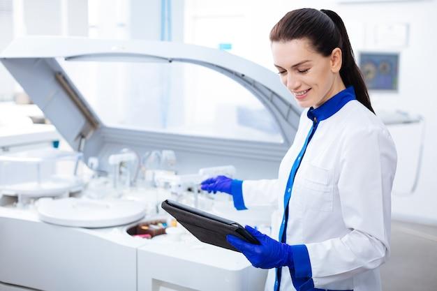 科学は軽いです。愛らしい笑顔と遠心分離機に手を伸ばしながらタブレットを見ている美しい優しいインスピレーションを得た女性インターン