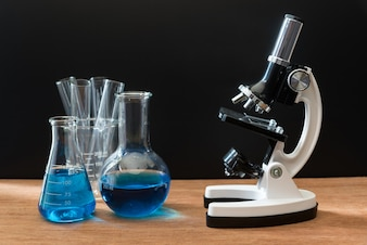 Science laboratory test tubes and white microscope on wooden table with black background
