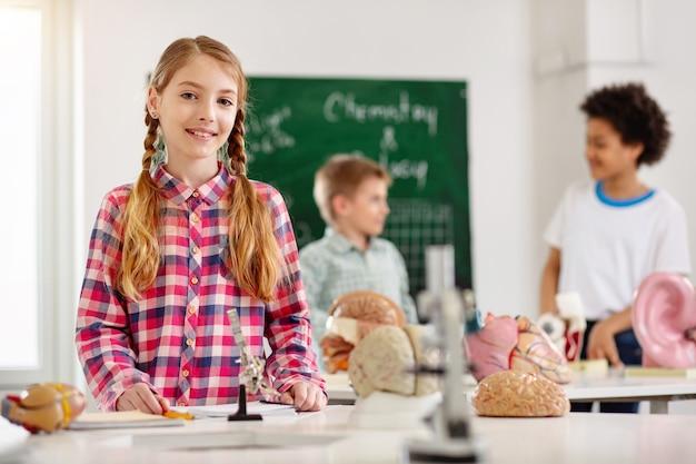 과학 수업. 과학 수업을하는 동안 테이블에 서있는 좋은 똑똑한 소녀