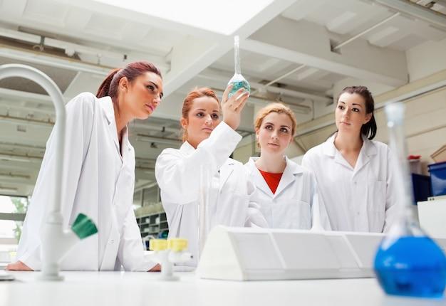フラスコ内の液体を見ている科学学生