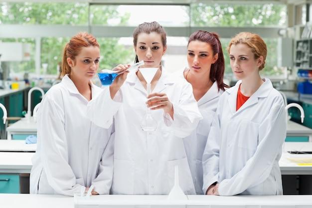 フラスコに液体を注ぐ科学学生