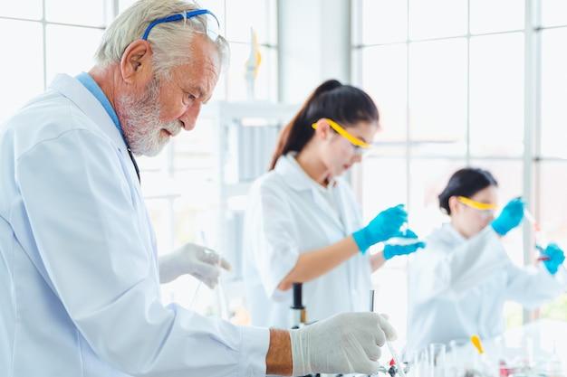 Преподаватель естественных наук и команда студентов, работающих с химическими веществами в лаборатории