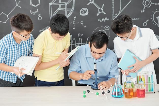 현미경을 통해 보는 과학 교사, 그 주위에 서서 공책에 쓰는 학생들
