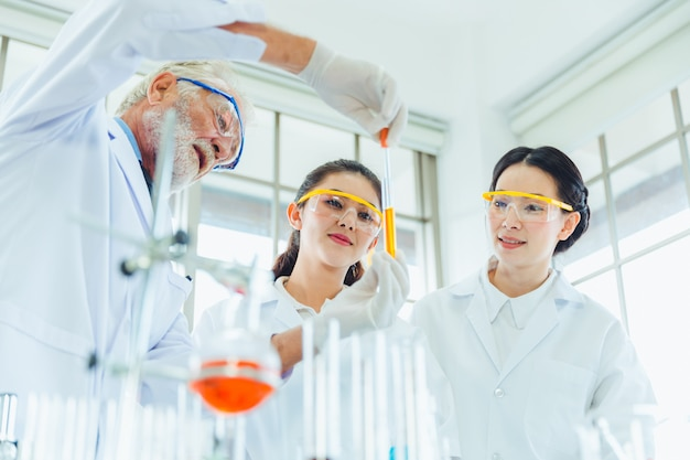 Science teacher and students team working with chemicals in lab