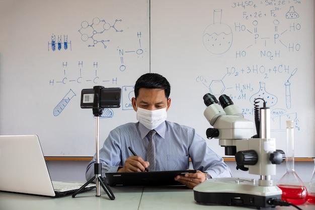 얼굴 마스크를 쓰고 교실에서 가르치는 과학 교사