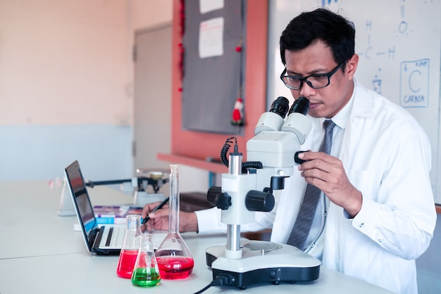 Science teacher    teaching with using computer and microscope in the classroom