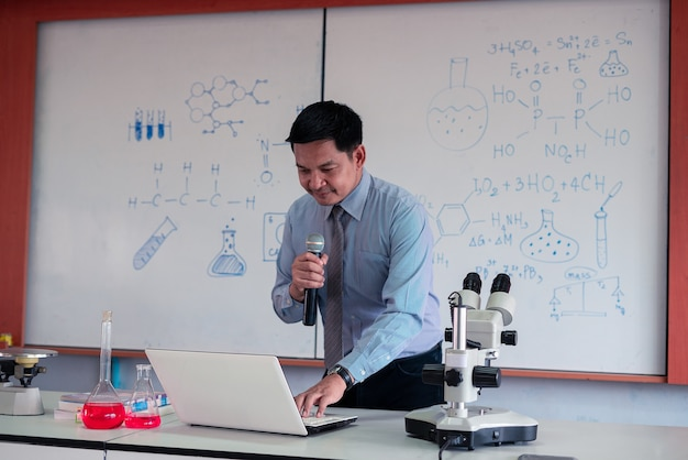 마스크를 쓰고 교실에서 노트북으로 온라인으로 가르치는 과학 교사