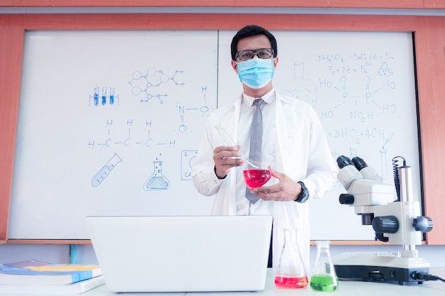 Science teacher wearingmask and   teaching with using microscope in the classroom