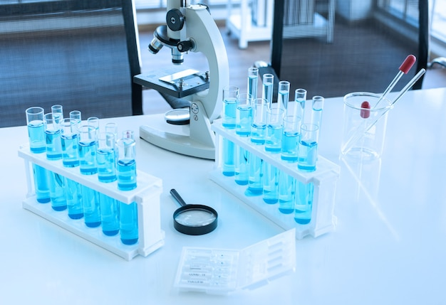 Scientific equipment on lap table such as microscope ,beaker, test tube with blue fluid , pipet and magnifying glass
