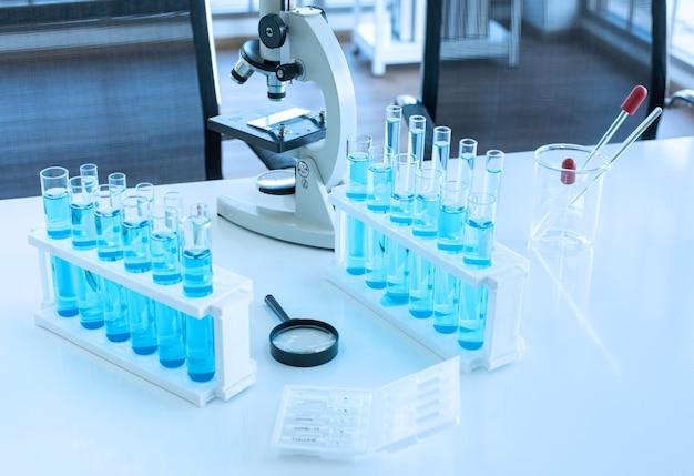 Научное оборудование на рабочем столе, такое как микроскоп, химический стакан, пробирка с голубой жидкостью, пипетка и увеличительное стекло.