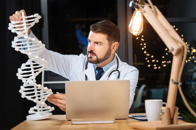 과학적 천재. dna 모델을 들고 과학적 연구를하면서 연구하는 스마트 전문 유전 연구원