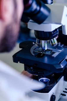 Scientific handling a light microscope examines a laboratory sample for pharmaceutical bioscience research.
