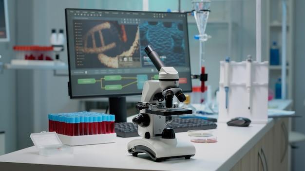 Научный микроскоп на лабораторном столе с исследовательскими инструментами