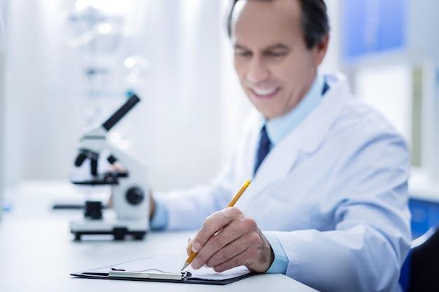 과학 보고서. 과학자의 선택적 초점은 실험실에서 테이블에 누워 노트