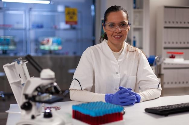 Научная женщина, сидящая в лаборатории с инструментами