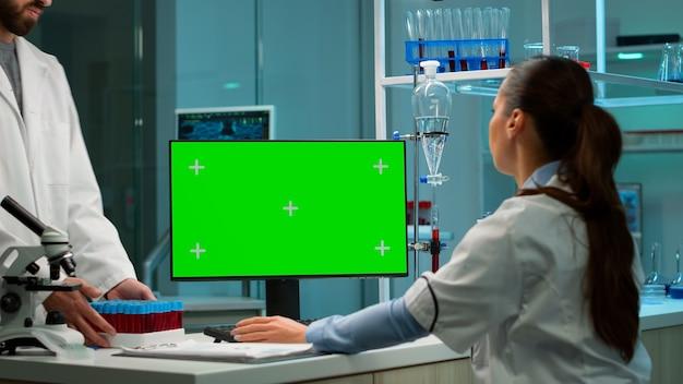Ученый анализирует образец крови и печатает на компьютере с зеленым экраном, цветным ключом. в фоновом режиме исследователь лаборатории человек обсуждает с врачом о разработке вакцины.