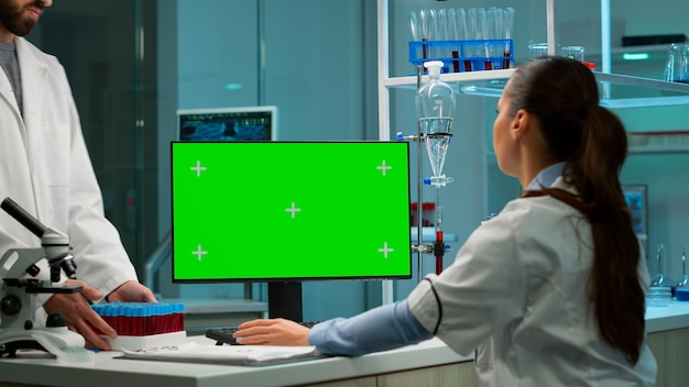 Scientist analysing blood sample and typing at computer with green screen, chroma key display. in background man lab researcher discussing with doctor about vaccine developent.
