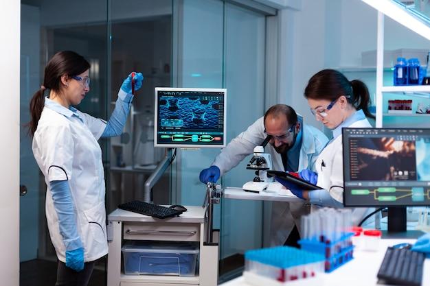 Ученый анализирует образец крови в vacutainer с исследовательской группой, просматривающей микроскоп