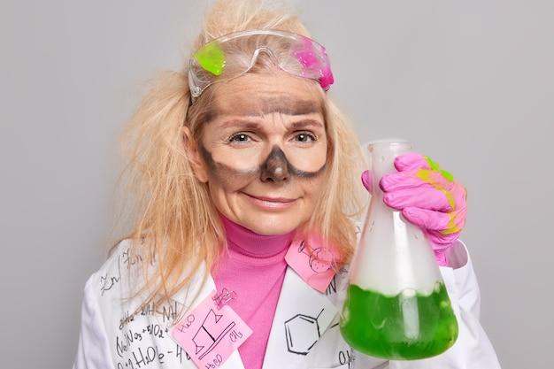 Ученый на работе проводит эксперимент в лаборатории держит стеклянную посуду с зеленой жидкостью, имеет грязное лицо после химического эксперимента, носит медицинский халат и перчатки, изолированные на сером
