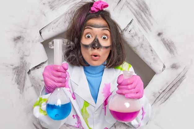 Ученый-биохимик работает над химическим экспериментом, держит стеклянные колбы в одиночестве, будучи научным сотрудником лаборатории, одетый в белый халат, пробивает бумажную дыру